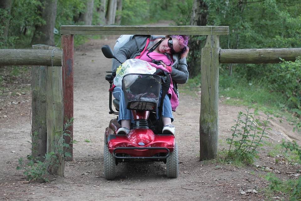 Wheelchair user in the park limboing under a high fence