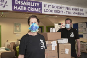 Photo of Mel and Des with masks on and stood next to big boxes of PPE