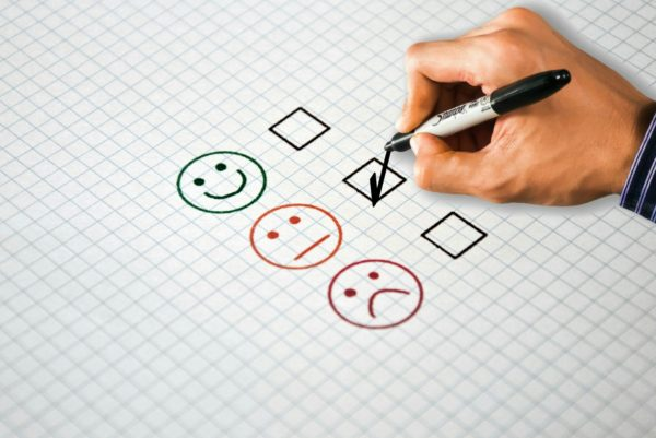 Piece of gridded paper with a happy, neutral and sad faces next to tick boxes, with a hand holding a pen ready to tick the neutral box