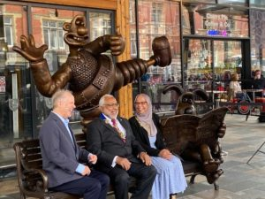 Photo of the bronze Wallace and Gromit bench with Nick Park anf other Preston leaders.
